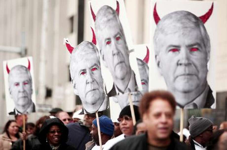 Protestors carry signs that depict Michigan's Governor Rick Snyder as a devil at a rally in front of the U.S. Courthouse in Detroit where Detroit's bankruptcy eligibility trial on Oct. 28, 2013. Photo: Getty Images / 2013 Getty Images