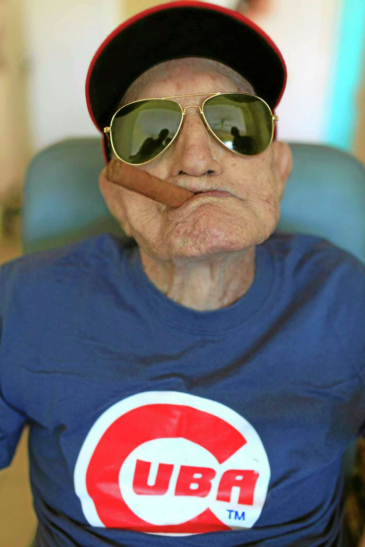 """In this April 25, 2013 file photo, Conrado Marrero, the world's oldest living former Major League Baseball player, poses for a photo on his 102 birthday at his home in Havana, Cuba. Family members say Marrero died Wednesday in Havana, just two days short of his 103rd birthday. Marrero was a diminutive right-hander who went by the nickname """"Connie"""" when he pitched for the Washington Senators in the 1950s."""