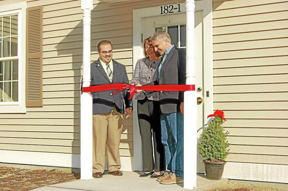 First Selectman Michael Criss joins The Washington Agency owners and brokers Joanne Donne and Tony Gioia at the ribbon cutting ceremony for the agency's new location. Photo: Jenny Golfin—Register Citizen