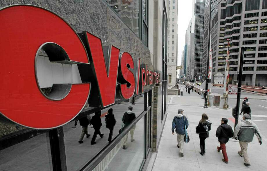 FILE- In this Feb 7, 2012 file photo, pedestrians walk pass a CVS store in Chicago.  CVS Caremark Corp. said Tuesday, Nov. 6, 2012, that its third-quarter earnings climbed 16 percent. The drugstore operator and pharmacy benefits manager posted revenue increases in both businesses, benefiting from new customers won from rivals, and raised its full-year earnings outlook. (AP Photo/M. Spencer Green, File) Photo: AP / AP