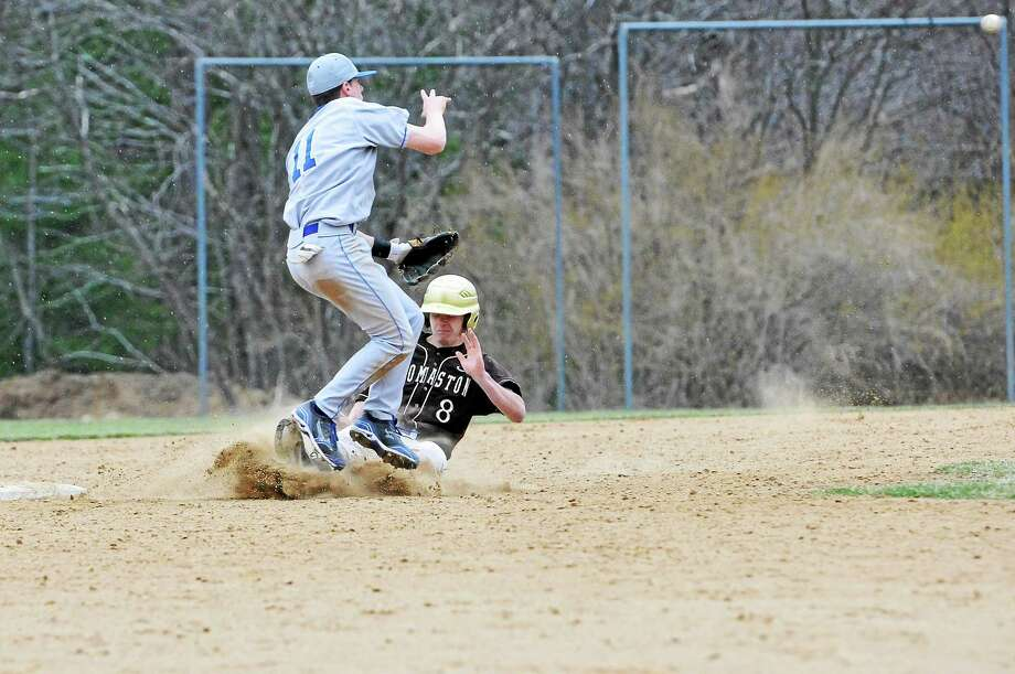 Thomaston's Matt Tehan slides into second base, successfully breaking up a double play, as Lewis Mills' Max Wadington jumps over him to make the throw. Photo: Laurie Gaboardi — Register Citizen