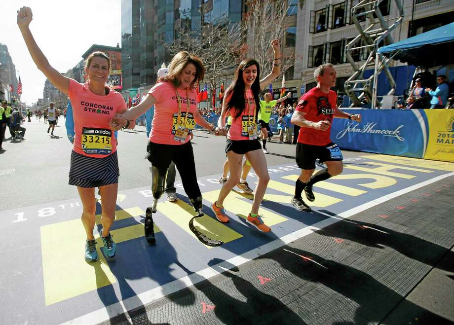 Double amputee Celeste Corcoran, center, a victim of last year's bombings, reaches the finish line of the 118th Boston Marathon, Monday, April 21, 2014, in Boston, with the aid her sister Carmen Acabbo, left, and daughter Sydney, right, who was also wounded last year. (AP Photo/Elise Amendola) Photo: AP / AP