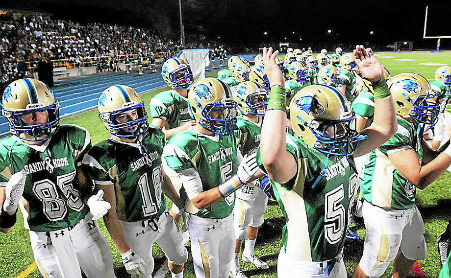 The Newtown football team celebrates after scoring first against Bethel in the first half on 9/20/2013.  Photo by Arnold Gold/New Haven Register Photo: Journal Register Co.