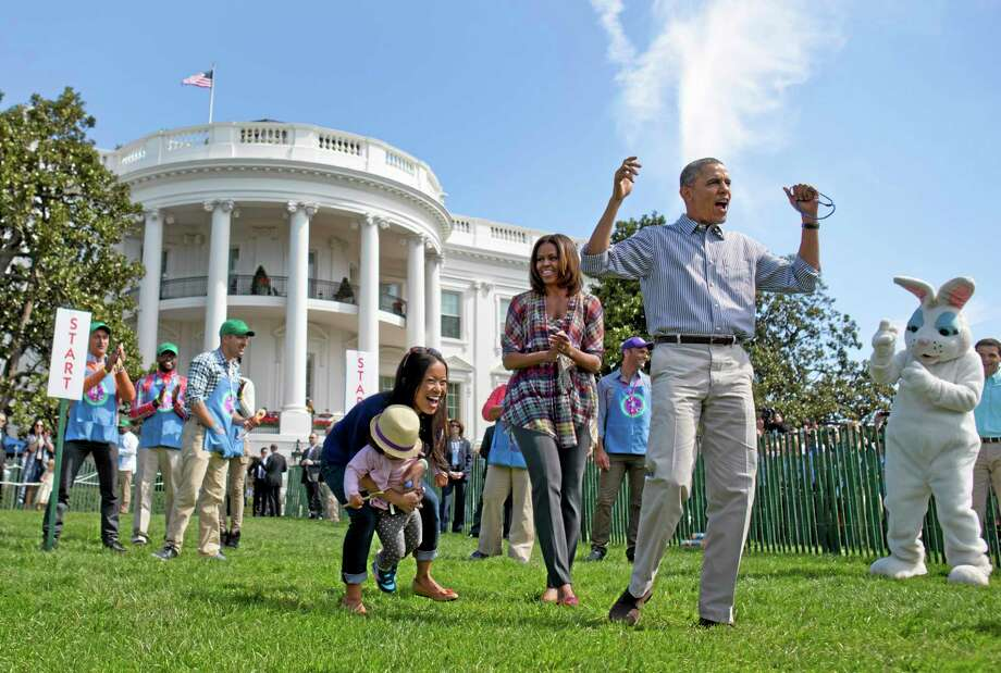 President Barack Obama and first lady Michelle Obama cheer and applaud as they host the White House Easter Egg Roll on the South Lawn of the White House is Washington, Monday, April 21, 2014. Thousands of children gathered at the White House for the annual Easter Egg Roll. President Barack Obama and first lady Michelle Obama kicked off the festivities on the White House South Lawn. This year's event features live music, cooking stations, storytelling, and of course, some Easter egg rolling.(AP Photo/Carolyn Kaster) Photo: AP / AP