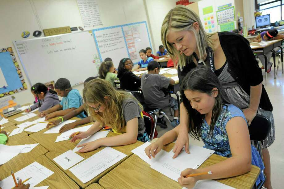 """Amy Lawson, a fifth-grade teacher at Silver Lake Elementary School in Middletown, Del., helps student Melody Fritz with an English language arts lesson Oct. 1, 2013. Silver Lake has begun implementing the national Common Core State Standards for academics. Remembering the plot of a short story is no longer good enough in Lawson's fifth-grade classroom. Now, students are being asked to think more critically -- what, for example, might a character say in an email to a friend. """"It's hard. But you can handle this,"""" Lawson tells them. Welcome to a classroom using the Common Core State Standards, one of the most politicized and misunderstood changes in education for students and their teachers in grades kindergarten through high school. Photo: Steve Ruark—The Associated Press  / FR96543 AP"""