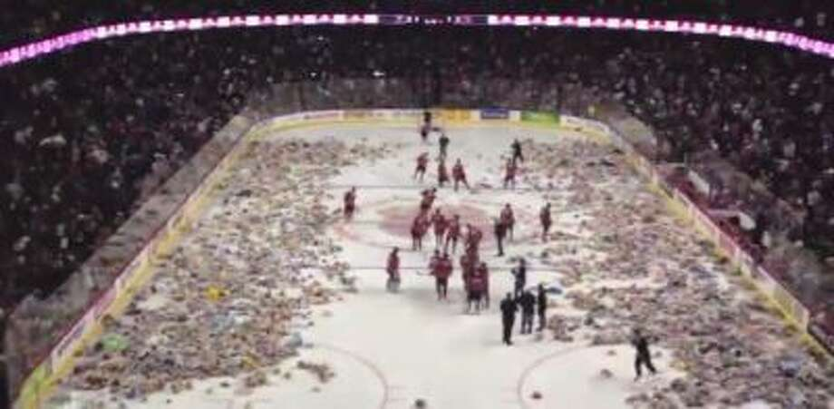 Fans of the Calgary Hitmen throw teddy bears on the ice in this screengrab.