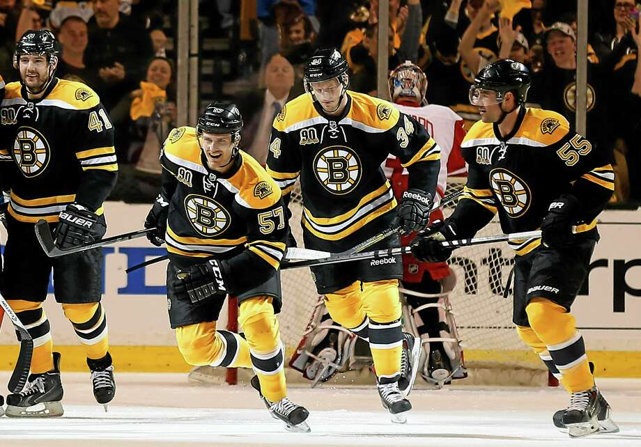 Boston Bruins' Justin Florek (57) leads the charge to the bench with teammates Andrej Meszaros (41), Carl Soderberg (34) and Johnny Boychuk after scoring against the Detroit Red Wings during the first period of Game 2 of a first-round NHL hockey playoff series in Boston, Sunday, April 20, 2014. (AP Photo/Winslow Townson) Photo: AP / FR170221 AP