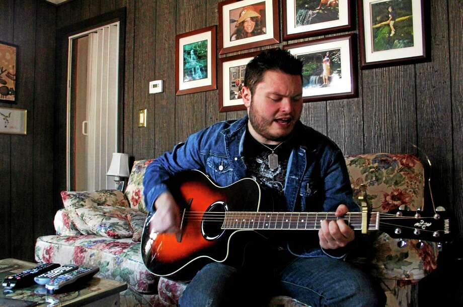 Country singer Cody Wolfe performs a song in his living room on Sunday, April 20, 2014, in Torrington. Wolfe announced last week that he's moving to Nashville to pursuit his dream of becoming a country star. Photo: Esteban L. Hernandez — Register Citizen