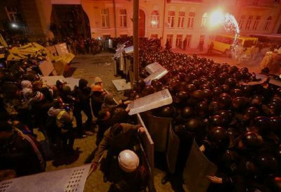 A firefighter throws a flare back to protesters during clashes with police guarding presidential administration building in downtown Kiev, Ukraine, on Sunday, Dec. 1, 2013.