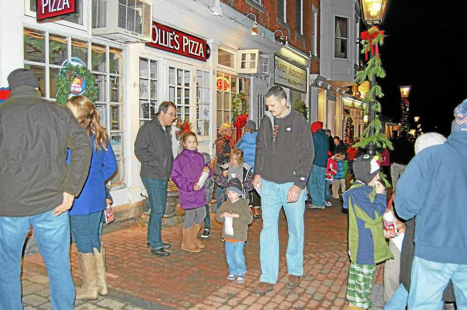 Litchfield residents take part in a holiday stroll in Litchfield center on Sunday. Photo: Isaac Avilucea — Register Citizen