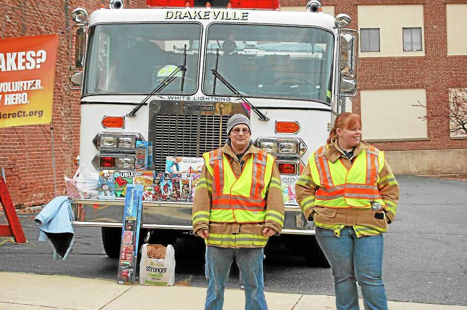 Drakeville Volunteer Firefighters Nick Ross, left, and Kellsey Schaffer collect gifts on Water Street on Sunday. Photo: Photos By Isaac Avilucea — Register Citizen