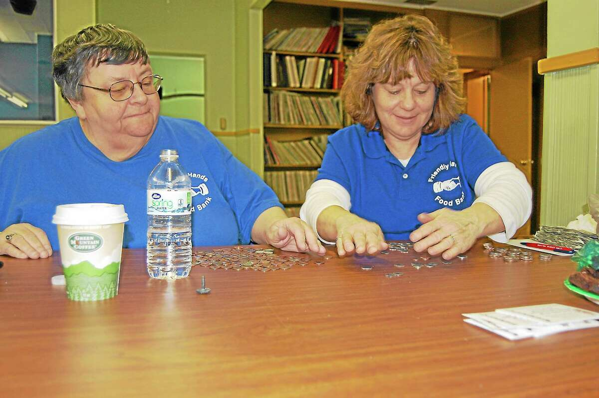 Maureen Hubert and Tina Hasapis count money collected by the Drakeville Volunteer Fire Department for the Friendly Hands Food Bank.
