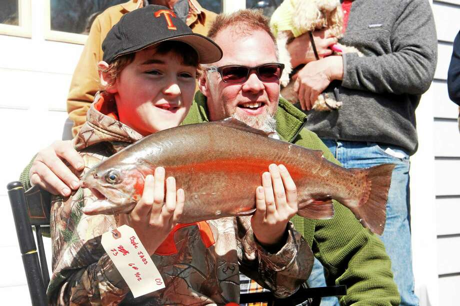 Bodie Jabs, 10, holds up his winning catch next to his father, Bobby, on Saturday, April 19, 2014, during the Riverton Fishing Derby . The winning trout measured 23 inches and weighed 6 pounds and took about 20 minutes to reel in. Photo: Esteban L. Hernandez — Register Citizen