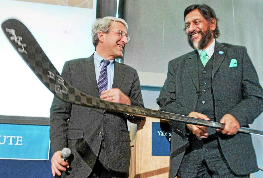 """Yale University President Peter Solovey, left, presents Dr. Rajendra Pachauri with a souviner hockey stick from the NCAA Championship Yale hockey team of 2013. Dr. Pachauri led a conference on climate change Thursday. The hockey stick was used in the """"Frozen Four"""" and also is shaped like the graph representing climate change. Photo: Melanie Stengel — NEW HAVEN Register    / PETER HVIZDAK"""