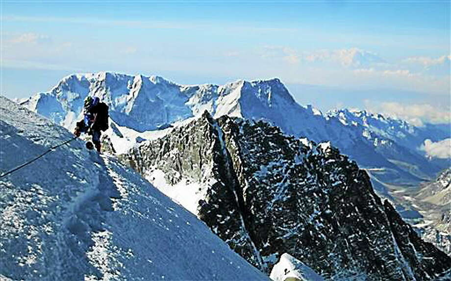In this May 2013 file photo released by mountain guide Adrian Ballinger of Alpenglow Expeditions, a climber pauses on the way to the summit of Mount Everest, in the Khumbu region of the Nepal Himalayas. An avalanche swept down a climbing route on Mount Everest early Friday killing at least 12 Nepalese guides and leaving three missing in the deadliest disaster on the world's highest peak. Photo: Associated Press  / ALPENGLOW EXPEDITIONS