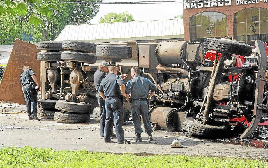 Police inspect an overturned dump truck that collided with a bus causing a chain reaction at the foot of Avon Mountain on Route 44 in Avon on July 29, 2005. Photo: Steven Lee Miller — The Associated Press  / AP