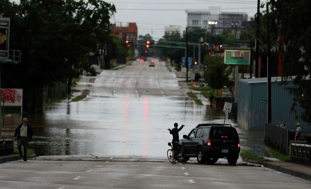 A bicyclist chats with a motorist on the Durham Bridge with water from the White Oak Bayou covering it after heavy rain from Hurricane Harvey fell overnight, Sunday, Aug. 27, 2017, in Houston. Photo: Karen Warren, Houston Chronicle / @ 2017 Houston Chronicle