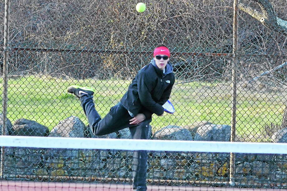 Torrington's Ethan Barbieri serves during his and Nick Mancini's 8-5 win in doubles to clinch the match for the Red Raiders. Photo: Pete Paguaga — Register Citizen