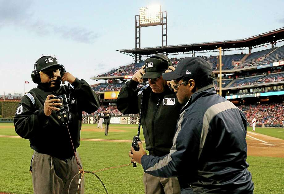 Umpires Adrian Johnson, left, and Larry Vanover, center, listen to an instant replay call during the first inning of Wednesday's game between the Phillies and the Milwaukee Brewers in Philadelphia. Photo: Michael Perez — The Associated Press  / FR168006 AP