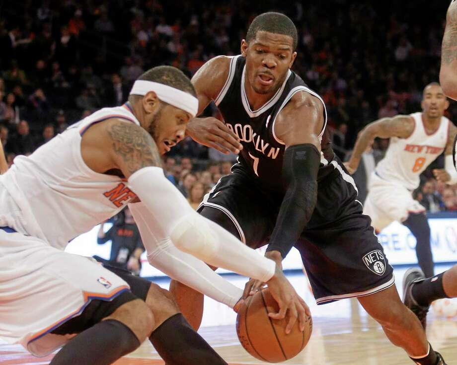 The New York Knicks' Carmelo Anthony, left, may sit out the team's final two games of the season. At right is the Brooklyn Nets' Joe Johnson. Photo: Frank Franklin II — The Associated Press  / AP