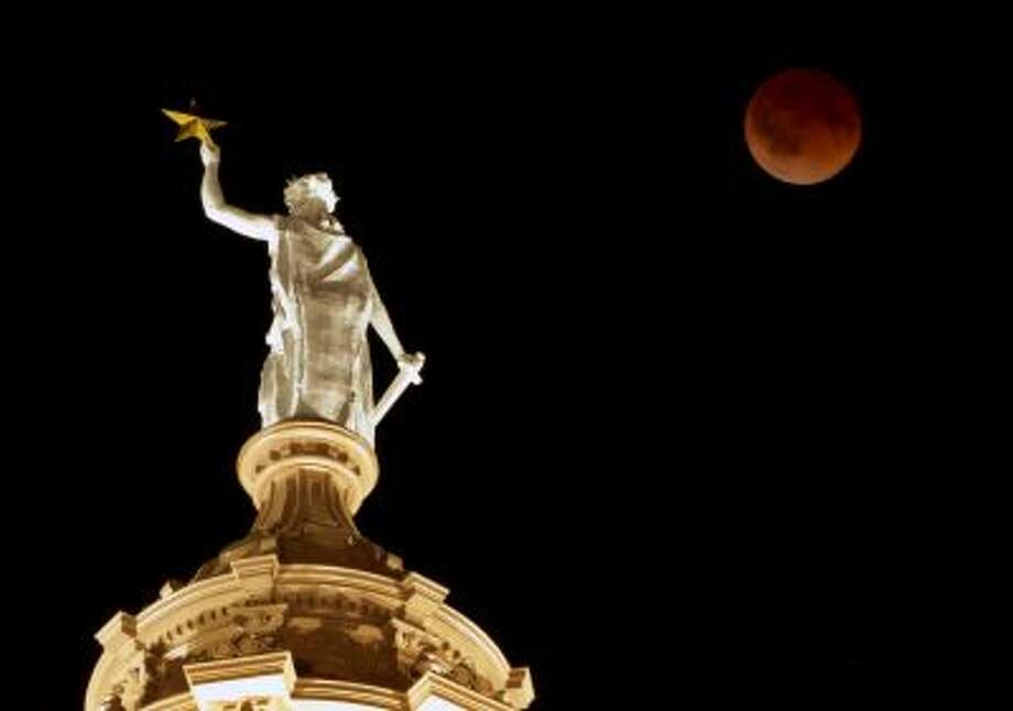The moon glows a red hue over the Goddess of Liberty statue atop the Capitol in Austin, Texas, during a total lunar eclipse Tuesday, April 15, 2014. Tuesday's eclipse is the first of four total lunar eclipses that will take place between 2014 to 2015. (AP Photo/Austin American-Statesman, Jay Janner) AUSTIN CHRONICLE OUT, COMMUNITY IMPACT OUT, INTERNET AND TV MUST CREDIT PHOTOGRAPHER AND STATESMAN.COM, MAGS OUT Photo: AP / AP2014