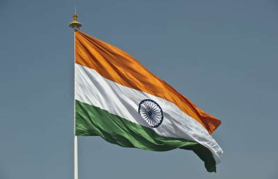 India's largest national flag flies from the highest flagpole in New Delhi on March 7, 2014. The Flag Foundation of India hoisted the largest flag in India, measuring 60 feet in width and 90 feet in length, and weighing 35 kilograms, on New Delhi's highest flagpole, at 207 feet, at the central park in Connaught Place in the capital. AFP PHOTO/Prakash SINGH        (Photo credit should read PRAKASH SINGH/AFP/Getty Images) Photo: AFP/Getty Images / 2014 AFP