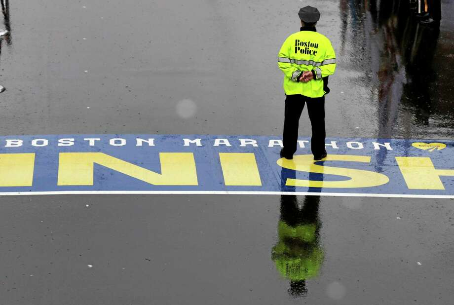 A Boston police officer pauses on the finish line during a tribute in honor of the one year anniversary of the Boston Marathon bombings, Tuesday, April 15, 2014 in Boston. (AP Photo/Charles Krupa) Photo: AP / AP