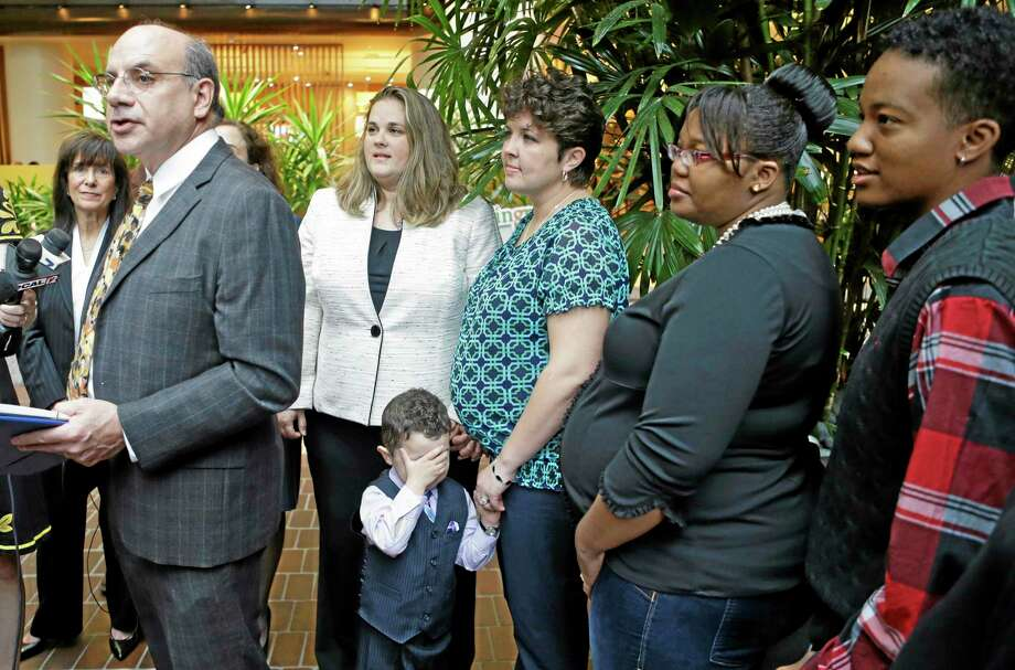 Attorney Al Gerhardstein, left, stands with several same-sex couples at a news conference, Friday, April 4, 2014, in Cincinnati. Civil rights attorneys are arguing in Federal Court on Friday that a federal judge should prohibit Ohio officials from enforcing the state's ban on gay marriage. (AP Photo/Al Behrman) Photo: AP / AP