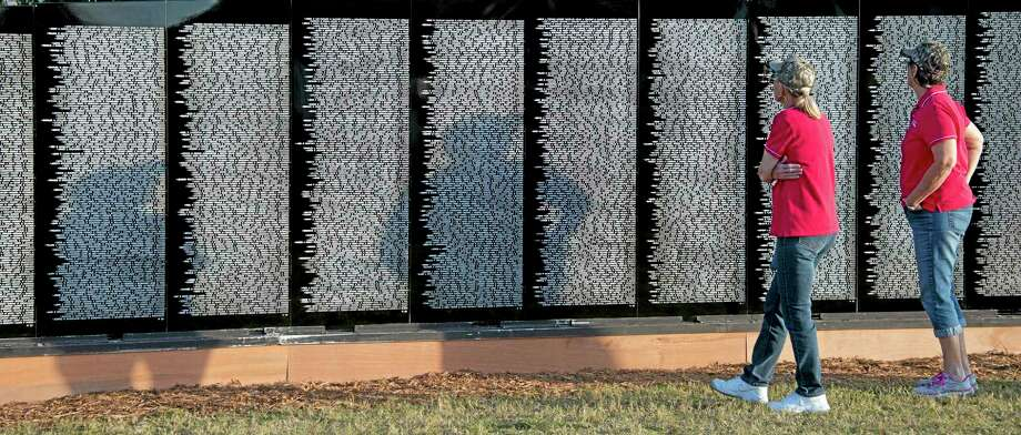 In this photo provided by the Florida Keys News Bureau, two women examine The Vietnam Traveling Memorial Wall, Thursday, April 10, 2014, in Key Largo, Fla. The 3/5 replica of the Vietnam Veterans Memorial wall in Washington, D.C., is to remain on display at a Florida Keys park through Sunday, April 13. (AP Photo/Florida Keys News Bureau, Andy Newman) Photo: AP / Florida Keys News Bureau