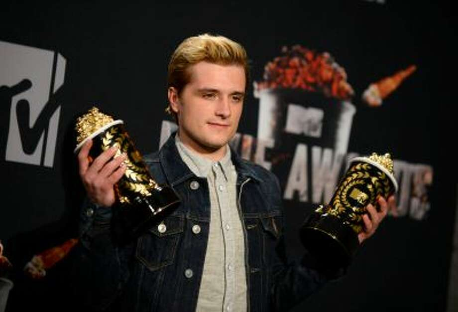 """Josh Hutcherson poses with his best male performance award and movie of the year award for """"The Hunger Games: Catching Fire"""" in the press room at the MTV Movie Awards on Sunday, April 13, 2014, at Nokia Theatre in Los Angeles. (Photo by Jordan Strauss/Invision/AP) Photo: Jordan Strauss/Invision/AP / AP2014"""