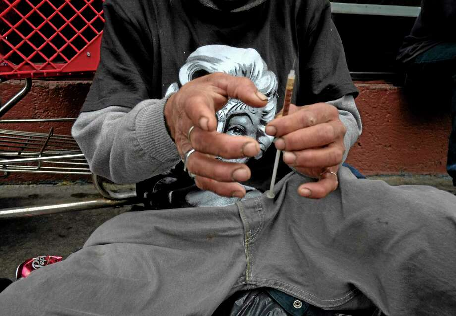 In this Monday, May 6, 2013 file photo, a drug addict prepares a needle to inject himself with heroin in front of a church in the Skid Row area of Los Angeles. The death of actor Philip Seymour Hoffman in February 2014 spotlighted the reality that heroin is no longer limited to the back alleys of American life. Once mainly a city phenomenon, the drug has spread to the country and suburbs. Photo: Jae C. Hong — File — The Associated Press  / AP