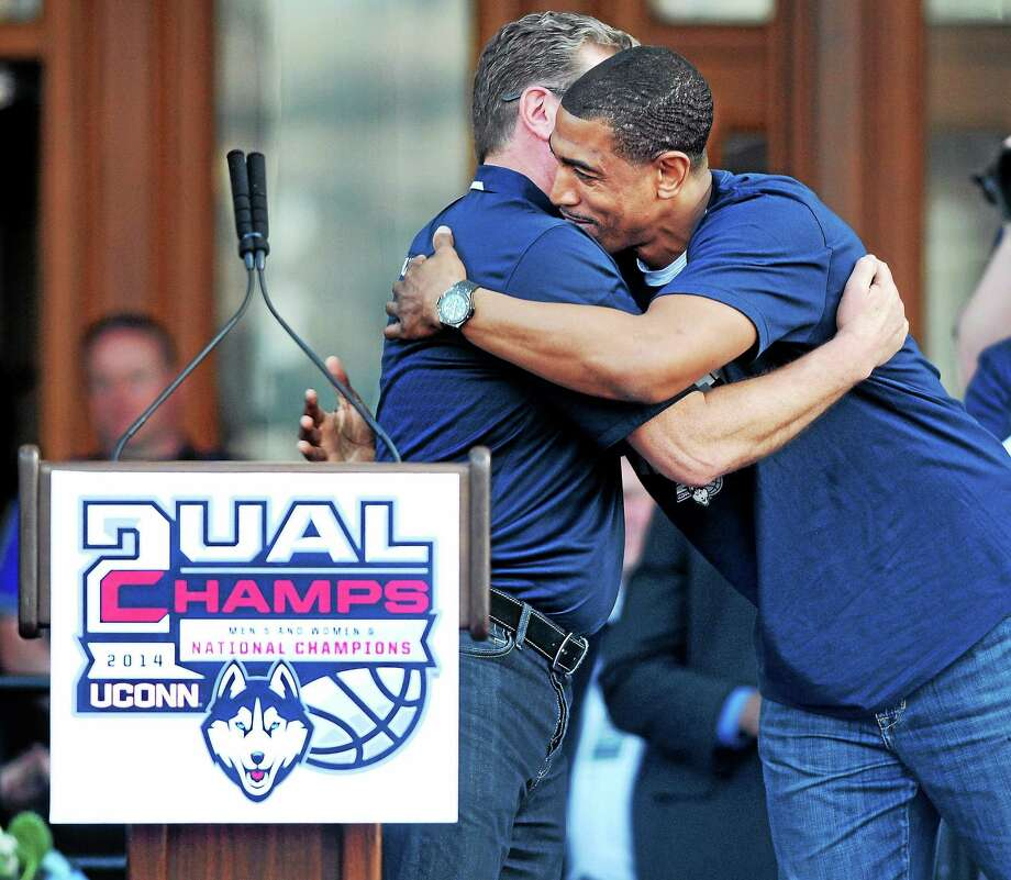 UConn men's basketball coach Kevin Ollie, right, hugs UConn women's coach Geno Auriemma at a victory rally in front of the Capitol Building in Hartford on Sunday. Photo: Arnold Gold — Register