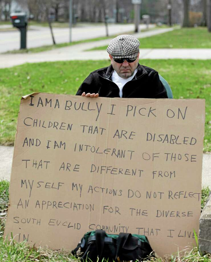 """Edmond Aviv sits on a street corner holding a sign Sunday, April 13, 2014, in South Euclid, Ohio declaring he's a bully, a requirement of his sentence because he was accused of harassing a neighbor and her disabled children for the past 15 years.  Municipal Court Judge Gayle Williams-Byers ordered Aviv, 62,  to display the sign for five hours Sunday. It says: """"I AM A BULLY! I pick on children that are disabled, and I am intolerant of those that are different from myself. My actions do not reflect an appreciation for the diverse South Euclid community that I live in."""" (AP Photo/Tony Dejak) Photo: AP / AP"""