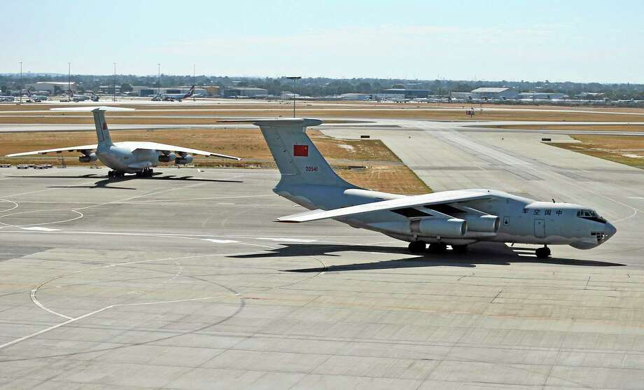 A Chinese  Ilyushin IL-76 aircraft, right, taxies at Perth International Airport after returning from the ongoing search operations for missing Malaysia Airlines Flight 370 in Perth, Australia, Sunday, April 13, 2014. Following four strong underwater signals in the past week, all has gone quiet in the hunt for the missing Malaysian airline, meaning the batteries on the all-important black boxes may have finally died. Despite having no new pings to go on, crews are continuing their search Sunday for debris and any sounds that could still be emanating. AP Photo/Rob Griffith) Photo: AP / AP