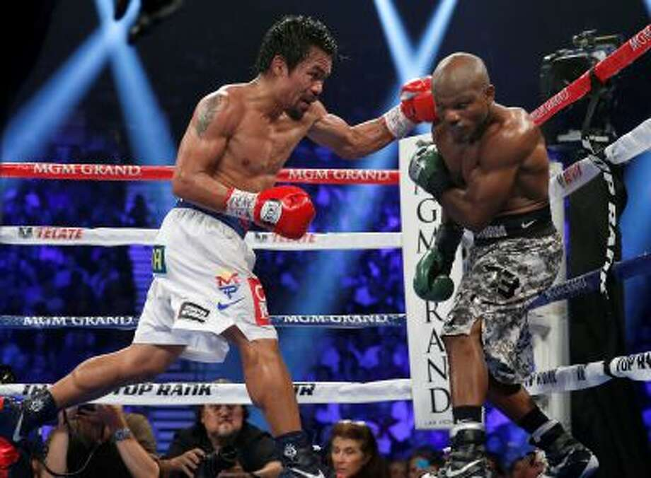 Manny Pacquiao, left, of the Philippines, drives Timothy Bradley into the ropes in their WBO welterweight title boxing bout Saturday, April 12, 2014, in Las Vegas. Pacquiao won by unanimous decision. (AP Photo/Isaac Brekken) Photo: AP / AP2014
