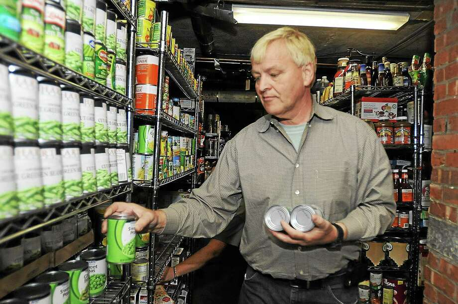 Laurie Gaboardi - Register Citizen Skip Hoxie, of the T-Town Torrington Chatter Facebook group, helps put away supplies collecting during a food drive at the Torrington Soup Kitchen. Photo: Journal Register Co.