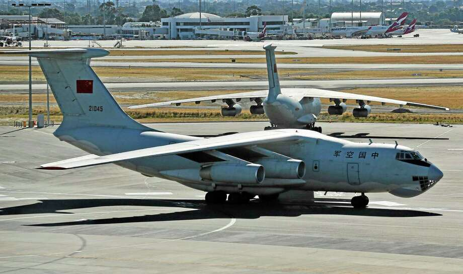 """A Chinese Ilyushin IL-76s aircraft taxies past another at Perth Airport, Australia, after returning from ongoing search operations for the missing Malaysia Airlines Flight 370, Saturday, April 12, 2014. With no new underwater signals detected, Australian Prime Minister Tony Abbott said Saturday that the massive search for the Malaysian jet would likely continue """"for a long time"""" as electronic transmissions from the dying black boxes were fading fast. (AP Photo/Rob Griffith, Pool) Photo: AP / AP POOL"""