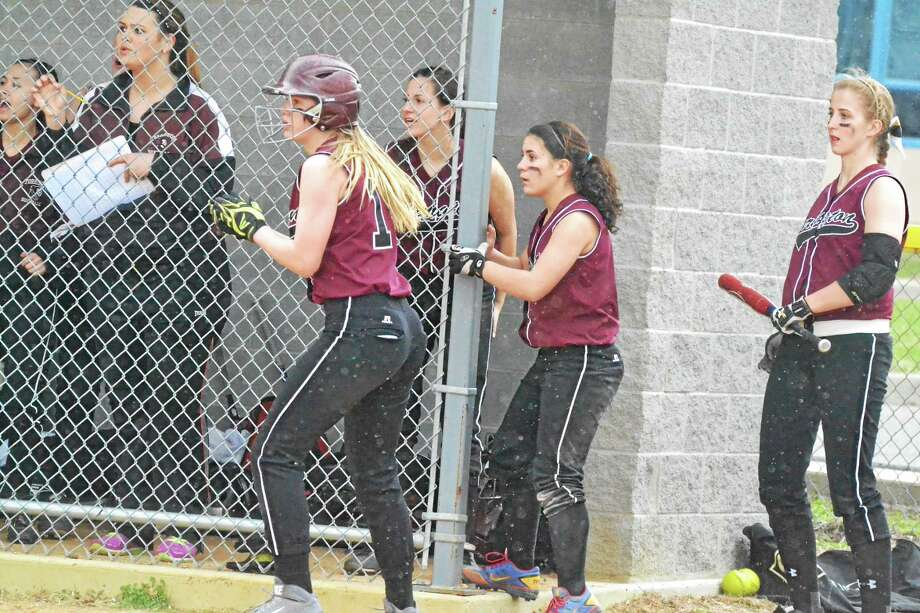 Torrington's Brittany Anderson (left) claps after she scores the first run of the game for the Red Raiders on a Marissa Morris base hit as Alexis Tyrell (middle) and Sydney Matzko (right) look on. Photo: Pete Paguaga — Register Citizen