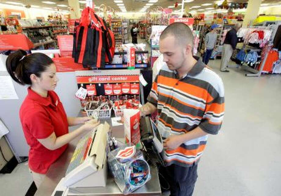 FILE - In this file photo taken Dec. 14, 2010, Family Dollar employee Pamela Ramos, left, assists John Conner with a purchase at a store in Waco, Texas. Family Dollar on Thursday, April 10, 2014 said it will be cutting jobs and closing about 370 underperforming stores as it looks for ways to improve its financial performance. It says it will also cut prices on about 1,000 basic items. (AP Photo/Tony Gutierrezfile, File) Photo: AP / AP