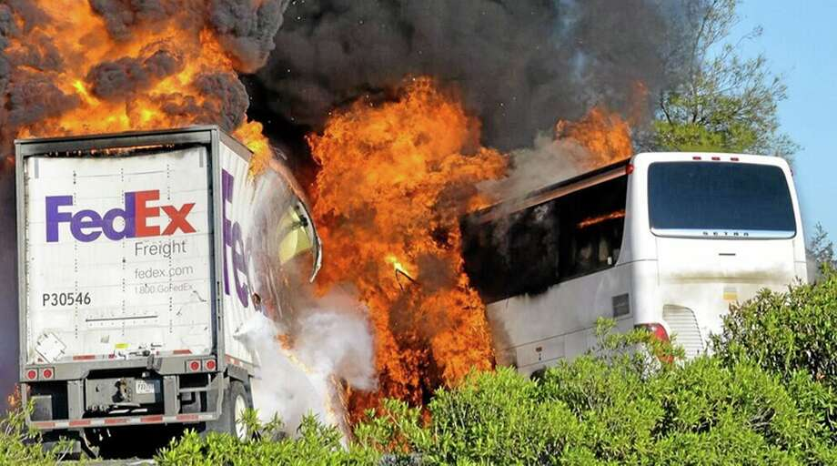 Massive flames are seen devouring both vehicles just after the crash, and clouds of smoke billowed into the sky  Thursday April 10, 2014 until firefighters had quenched the fire, leaving behind scorched black hulks of metal. The FedEx tractor-trailer crossed a grassy freeway median in Northern California and slammed into the bus carrying high school students on a visit to a college. At least nine were killed in the fiery crash, authorities said. (AP Photo/Jeremy Lockett) Photo: AP / Jeremy Lockett
