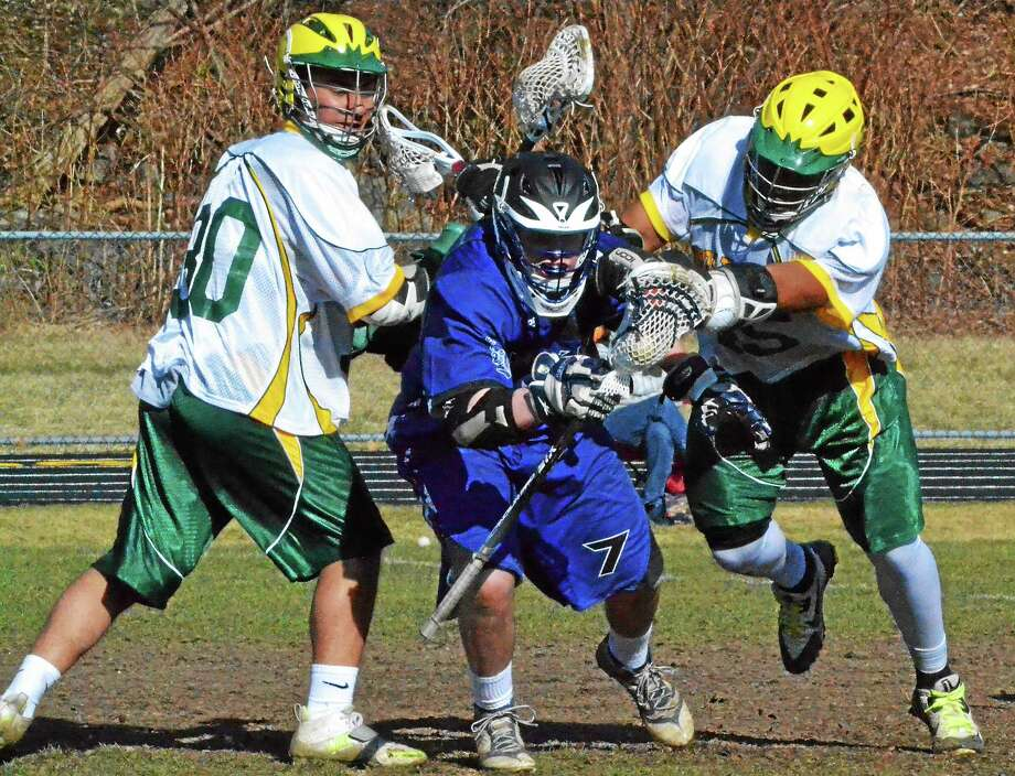 Lewis Millsí Connor Kennedy squeezes through Holy Crossí Jeremy Pire (left) and Breonte Nealy. Photo: Pete Paguaga — Register Citizen