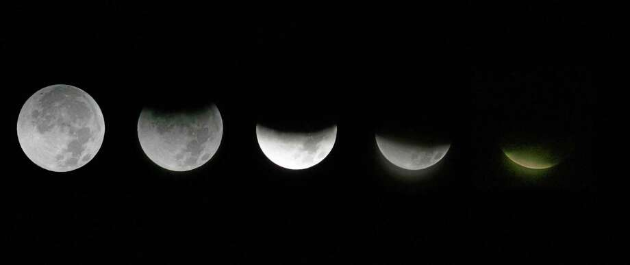 FILE - This combination of Saturday, Dec. 10, 2011 photos shows the different stages of the moon during a lunar eclipse as seen from the Griffith Observatory in Los Angeles. On Tuesday morning, April 15, 2014, the moon will be eclipsed by Earth's shadow and will be visible across the Western Hemisphere. The total phase will last 78 minutes. (AP Photo/Ringo H.W. Chiu) Photo: AP / FR170512 AP