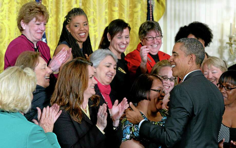 President Barack Obama greets people in the East Room of the White House in Washington, Tuesday, April 8, 2014, during an event marking Equal Pay Day. The president announced new executive actions to strengthen enforcement of equal pay laws for women. The president and his Democratic allies in Congress are making a concerted election-year push to draw attention to women's wages. Lilly Ledbetter is at left in green. (AP Photo/Susan Walsh) Photo: AP / AP