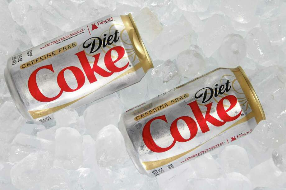 """FILE - This Monday, Oct. 15, 2012 file photo shows two cans of Caffeine Free Diet Coke on ice in Surfside, Fla. During a conference call with analysts Tuesday, Oct. 15, 2013, a Coca-Cola executive noted that Diet Coke was """"under a bit of pressure"""" because of people's concerns over its ingredients, alluding to the growing wariness of artificial sweeteners in recent years. Soda has been under fire from health advocates for several years now, and Americans have been cutting back on sugary fizz for some time. But in a somewhat newer development, diet sodas are falling at a faster rate than regular sodas, according to Beverage Digest, an industry tracker. (AP Photo/Wilfredo Lee, File) Photo: AP / AP"""