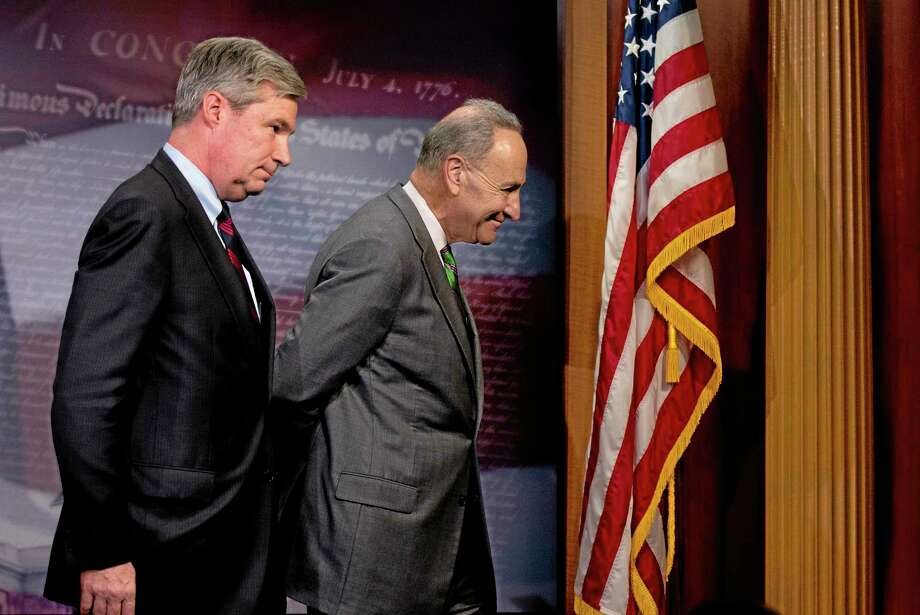 Sen. Charles Schumer, D-N.Y., right, followed by Sen. Sheldon Whitehouse, D-R.I. leave a news conference on Capitol Hill in Washington, Wednesday, April 2, 2014, where they talked about the Supreme Court decision in the McCutcheon vs. FEC case, in which the Court struck down limits in federal law on the aggregate campaign contributions individual donors may make to candidates, political parties, and political action committees.  (AP Photo/Manuel Balce Ceneta) Photo: AP / AP