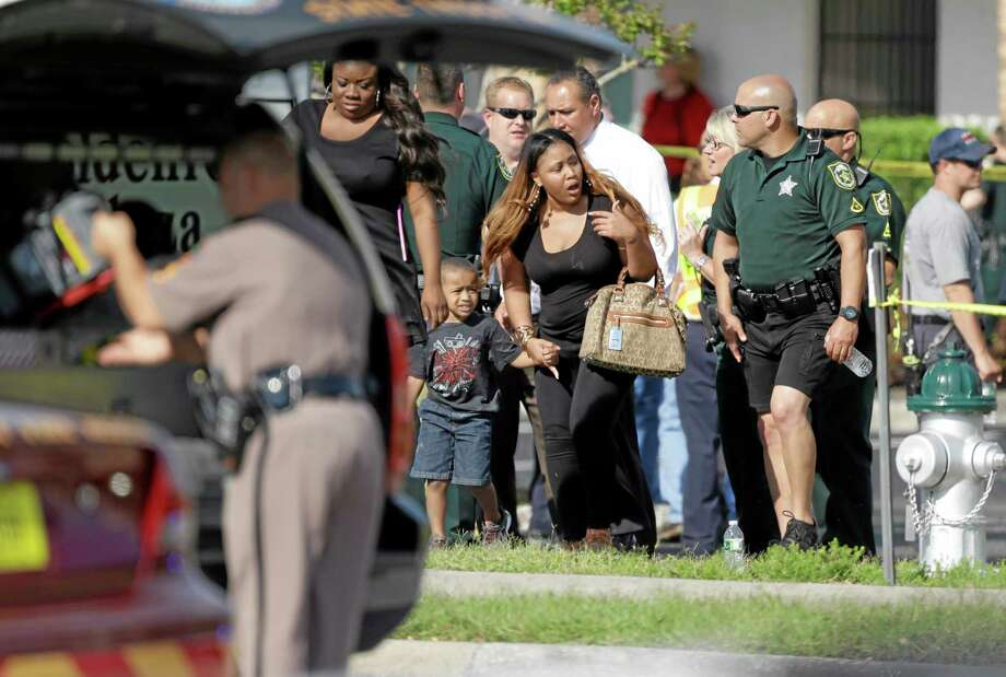 Parents with their children are escorted away with Orange County deputies after a vehicle crashed into a day care center, Wednesday, April 9, 2014, in Winter Park, Fla. At least 15 people were injured, including children. (AP Photo/John Raoux) Photo: AP / AP