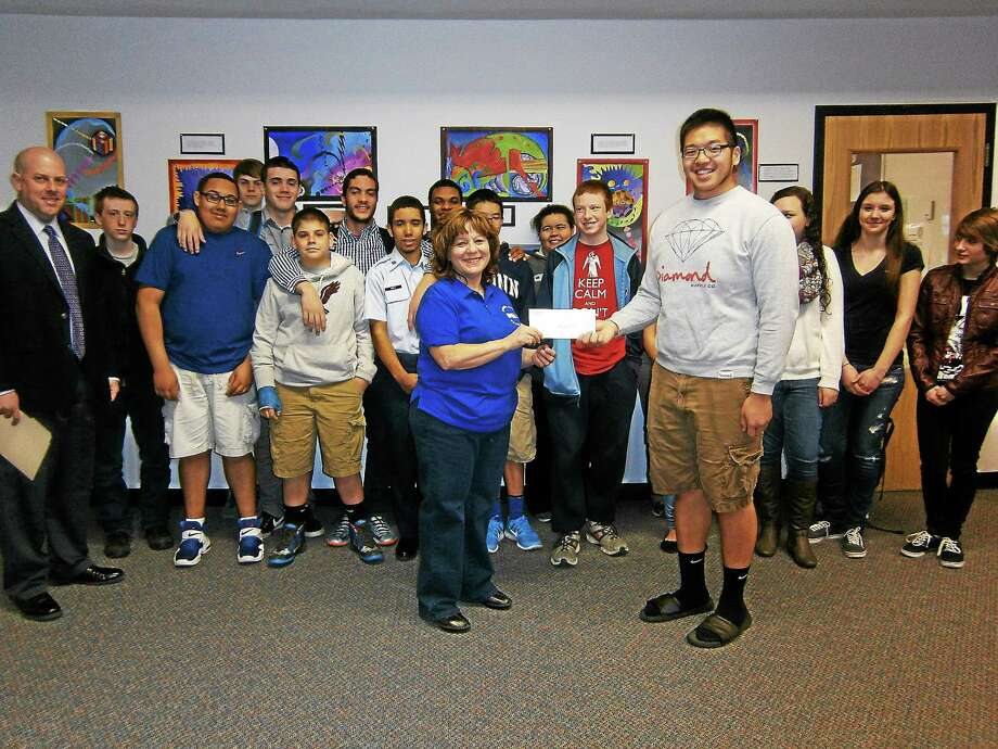 Torrington High School freshmen and senior students from two homerooms present Tina Hasapis, assistant director of Friendly Hands Foodbank, with a check for $200, their prize for being the homerooms that collected the most donations during a recent food drive. Photo: Contributed Photo