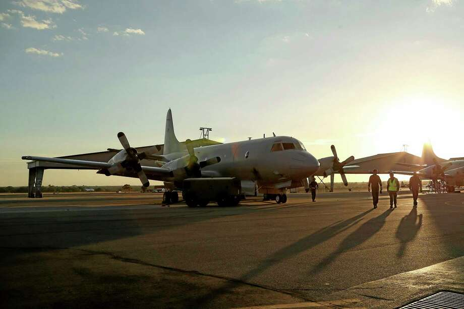 Flight crew from a Royal Australian Air Force P-3 Orion walk towards the aircraft at RAAF Base Pearce as it arrives back from the on-going search operations for missing Malaysia Airlines Flight 370 in Perth, Australia, Tuesday, April 8, 2014. Search crews have failed to relocate faint sounds heard deep in the Indian Ocean, possibly from the missing jetliner's black boxes whose batteries are at the end of their life. (AP Photo/Rob Griffith) Photo: AP / AP