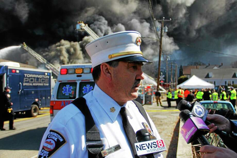 Chief Gary Brunoli talks with reporters as Torrington and dozens of other departments battled a five-alarm blaze at Toce Brothers Inc., a warehouse full of tires, on Albert Street in Torrington on April 3. Photo: Esteban L. Hernandez — The Register Citizen