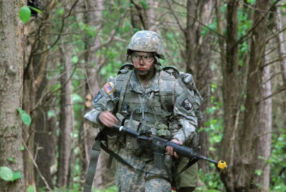 In a May 9, 2012 photo, Capt. Sara Rodriguez of the 101st Airborne Division walks through the woods during the expert field medical badge testing at Fort Campbell, Ky., on May 9, 2012.  Female soldiers are moving into new jobs in once all-male units as the U.S. Army breaks down formal barriers in recognition of what's already happened in wars in Iraq and Afghanistan.   (AP Photo/Kristin M. Hall) Photo: AP / AP